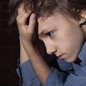 Ребенок нервничает и поэтому держит себя за волосы и за голову